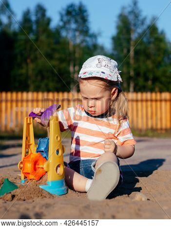 Little Girl Plays In Sandbox In Playground