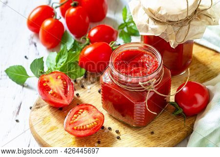 Tomato Paste, Home Preservation. Tomato Sauce Made From Ripe Tomatoes On A Wooden Tabletop.