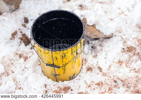 Empty Bucket From Under Waterproofing Compound Against The Background Of Snow