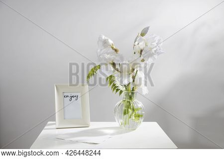 A Bouquet Of Three White Irises And A Fern In A Transparent Vase On The Table. Frame For Picture. Mo