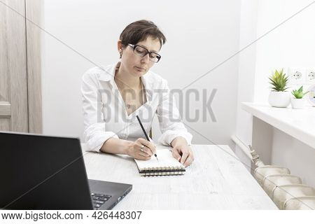 Middle-aged Woman With Short-haired Brunette In Glasses Works At A Laptop Near Window. Office Worker