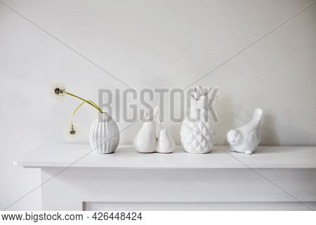White Figurines Of Pineapple, Pear, Bird, A Vase With Two Dandelions On The Background On A White Ta