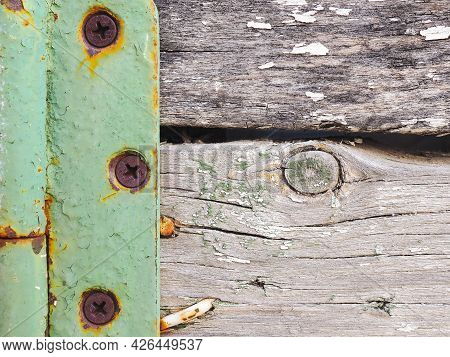 Fragment Of A Rustic Gate In A Fence Close-up. Old Gray Weathered Wooden Beams And Door Hinge. Vinta