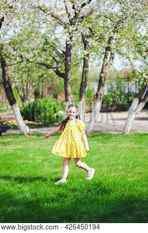 A Six-year-old Happy Girl Runs On A Green Lawn In The Park And Has A Good Time, Family Activity On T