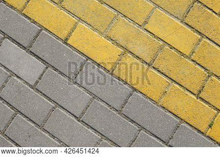 Diagonal Grey And Yellow Paving Slabs Top View. Bricks As Street Road, Paving Stone Texture. Abstrac