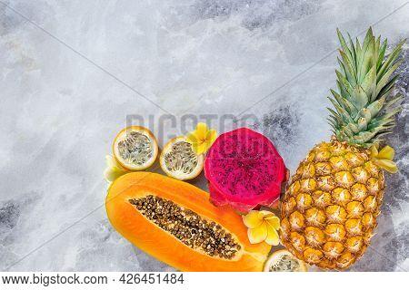 Ripe Pineapple, Papaya, Dragon Fruit, Passion Fruit On A Gray Background.