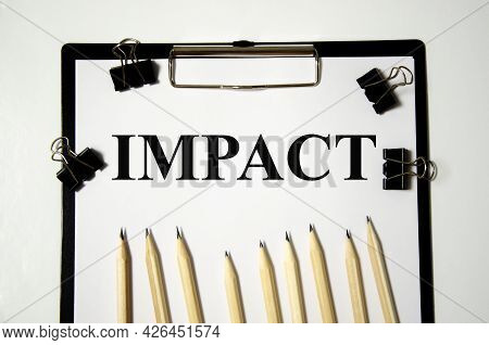 Impact The Word Is Written On A White Piece Of Paper With Pencils