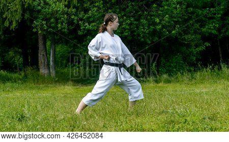 Teenage Girl Practicing Karate Kata Outdoors, Performs The Gedan-barai Or Downward Block