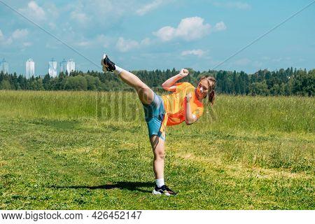 Teenage Girl In Casual Clothes Practicing Karate Kata Outdoors, Performs The Uro Mawashi Geri (hook
