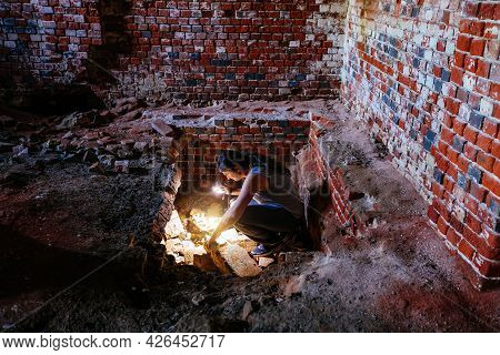 Archaeologist With Flashlight Examines The Old Crypt Under Church