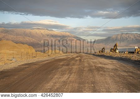 Wide Unpaved Road With Construction Site On The Side