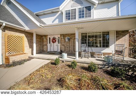 Exterior Of A House With Messy Front Yard Garden And Bricks