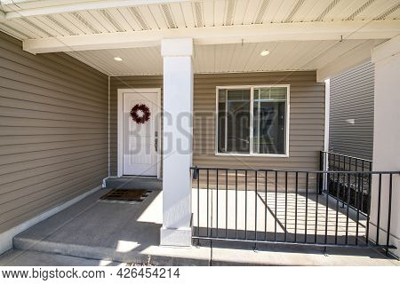 Front Porch Facade Of A House With Vinyl Wall Siding And Metal Railings