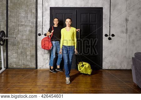 Two Women Enter Apartment With Travel Bags.