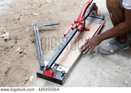 Worker Cutting Ceramic Tile With Tile Cutter Tool