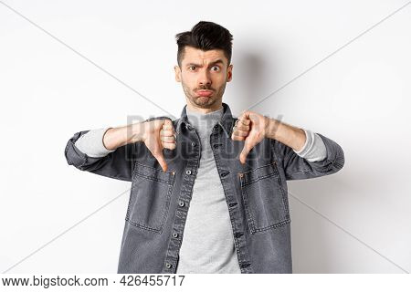 Disappointed Funny Man Frowning And Looking Upset, Showing Thumbs Down Displeased, Standing On White
