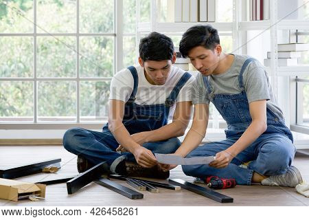 Two Carpenters Discussed The Type Of Bench Being Assembled. Handyman Installing Wooden Bench In New