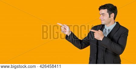 Young Caucasian Businessman In  Gray Shirt And Black Suit Pointing Both Finger In The Same Direction