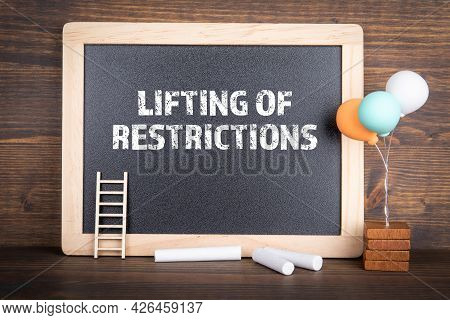 Lifting Of Restrictions. Chalk Board On A Wooden Background
