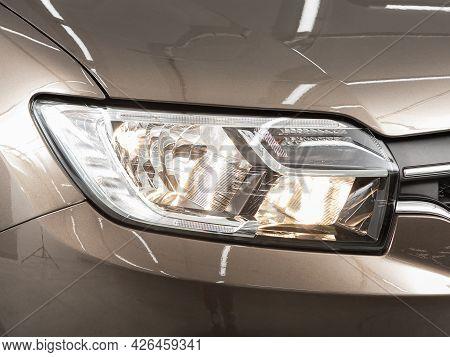 Novosibirsk, Russia - June 29, 2021: Renault Logan,  Close Up Of The Car Headlights. Exterior Closeu