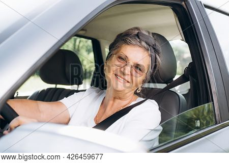 Joyful Mature Woman With Glasses Driving A Car And Looking At The Camera Through Open Window, Outdoo