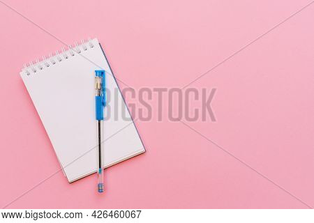 Open Spiral Notepad On Pink Background, Notepad And Blue Pen Lie On Paper, Flat Lay Concept