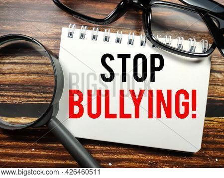Business Concept.text Stop Bullying On Notebook With Magnifying Glass And Glasses On A Wooden Backgr
