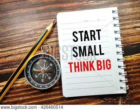 Business Concept.text Start Small Think Big On Notebook With Compass And Pencil On A Wooden Backgrou