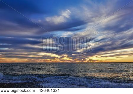 Colorful Sunset Over The Black Sea. The Sun Disappeared. There Are Purple Clouds In The Blue Sky. An