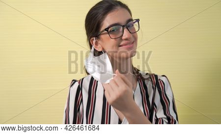Young Woman Take Off Face Mask Removing From Face Showing Concept Of The End Of Quarantine And Winni
