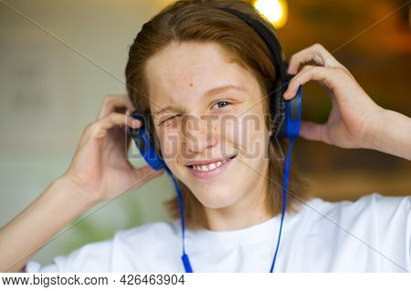 Red-haired Teenager Wearing Blue Headphones. He Listens To Music And Smiles.