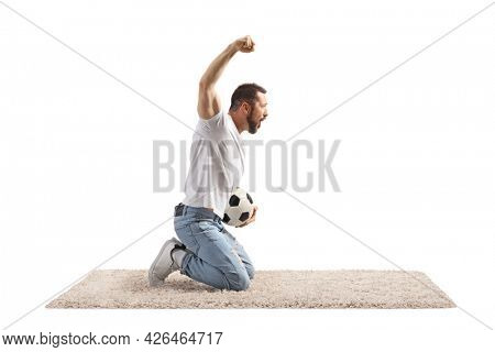 Young man holding a football, kneeling and cheering isolated on white background