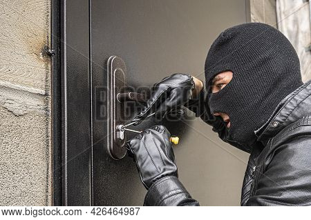 A Man In A Black Balaclava Mask Opens A Locked Door With A Lock Pick. The Robber Breaks Into The Hou