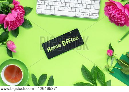 Remote Home Office On Green Desk. Workspace With Keyboard, Notepad, Glasses, Pen And Pencils. Bouque