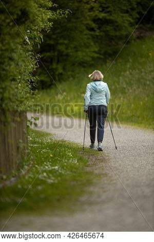 An elderly woman in nature Nordic walking outdoors. Healthy daily cardio routine.