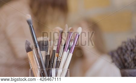 Makeup Brushes On Background Of Working Makeup Artist. Action. Set Of Professional Brushes On Blurry