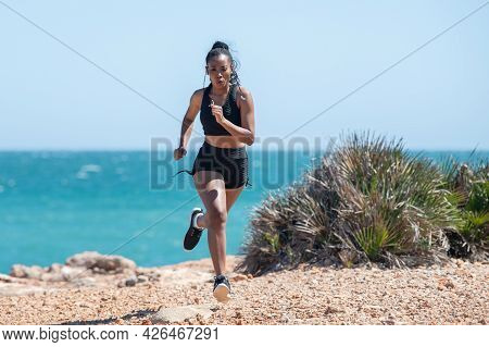 Afro American Woman Vigorously Running Near The Sea: Exercise And Strength Concept. Selective Focus.