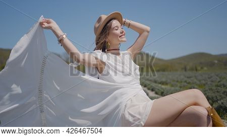 Beautiful Woman In White Dress Poses In Field. Action. Young Woman Waves Hem Of Dress In Wind. Woman