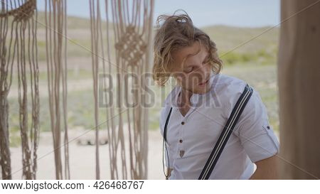 Attractive Man In Shirt Poses In Village. Action. Male Model Poses Sexually In Shirt At Country Hous
