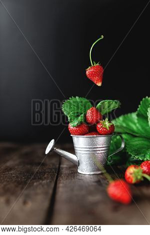 Fresh Wet Sweet Strawberries Levitation In Watering Can On Wooden Background Table, Black Wall, Gree