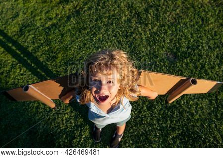 Laughing Child Playing With Toy Plane Wings In Summer Park. Innovation Technology And Success Concep