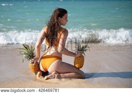 Playful Slim Woman In Sexy Bikini Stands Back Walks Away Sea Beach Holding Fresh Pineapple. Hot Summ