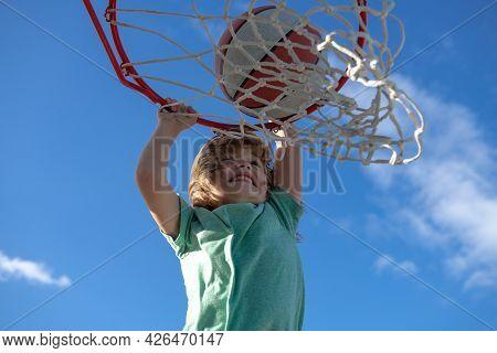 Closeup Portrait Of Kid Basketball Player Making Slam Dunk During Basketball Game.