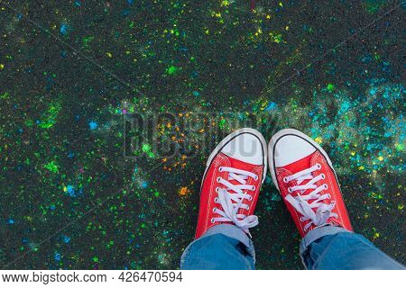Feet In Red Sneakers On Colorful Holi Powder Background, Top View.