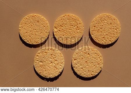 Set Of Natural Round Cellulose Sponges For Face Cleansing And Make Up Remowal On Brown Background.