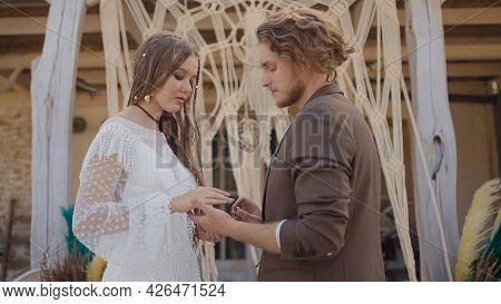 Wedding In Hippie Style. Action. Beautiful Couple Of Newlyweds Will Exchange Rings Under Crown. Hipp