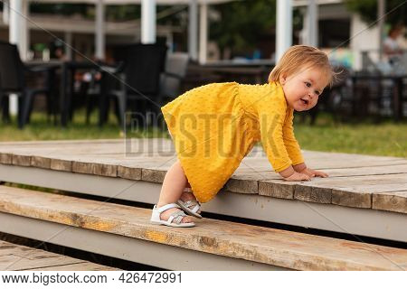 Cute Smiling Baby Girl In Yellow Dress Playing On The Steps. Outdoors. The Concept Of A Happy Childh