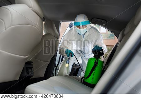 Employer In Protective Suit With Mask Disinfecting Inside Car