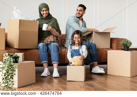 Happy Man, Woman And Girl Packing Or Unpacking Carton Boxes