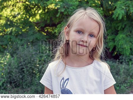 Adorable Child, Six-year-old Blonde Against The Background Of Nature, Portrait Of A Preschool Girl W
